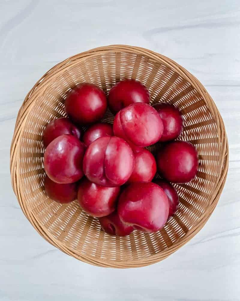 plums in a basket in a white background