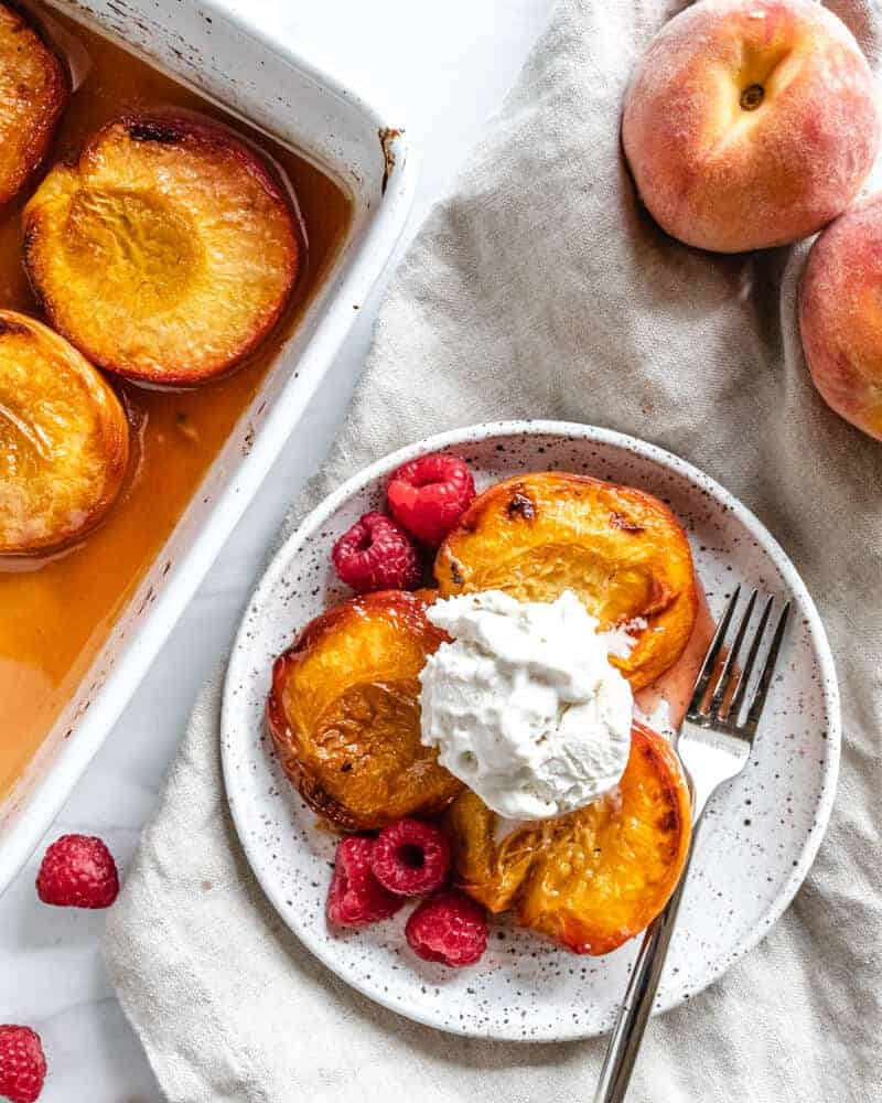 roasted peaches with raspberries topped ice cream with a white background
