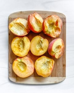 halved peaches on cutting board with white background
