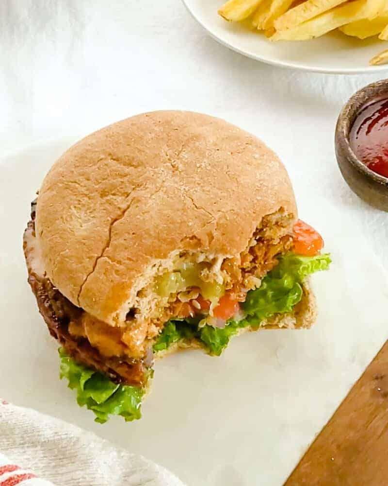 Half eaten vegan burger with Lettuce, tomato, onions and Sauce