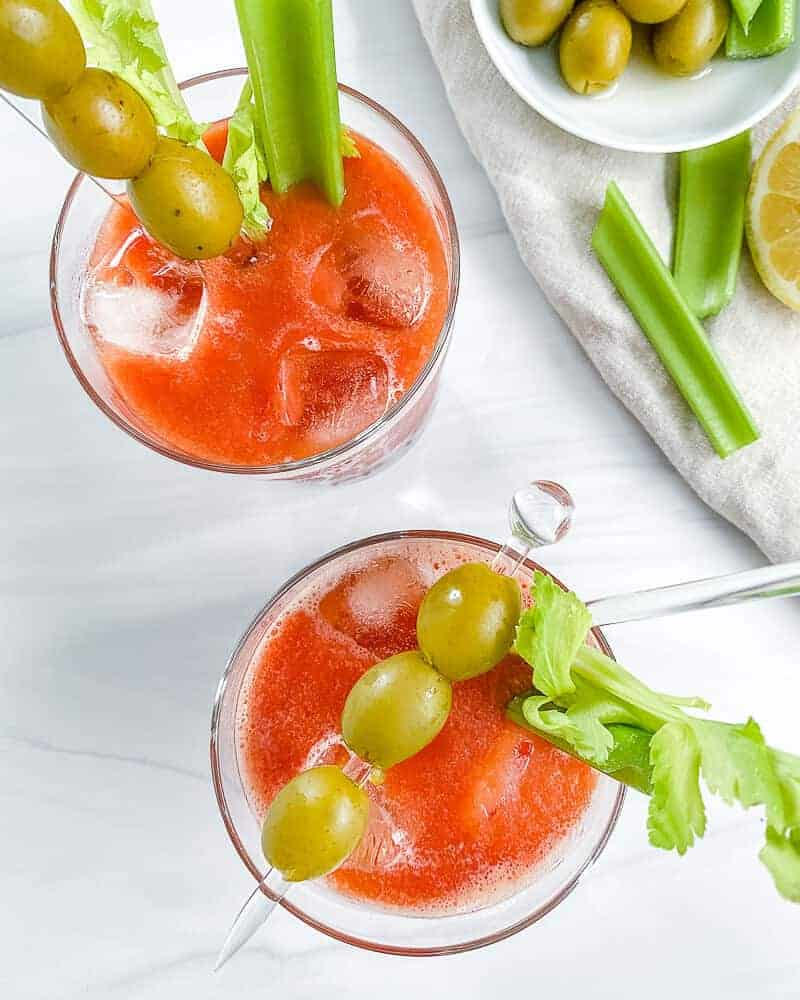 2 Virgin Bloody Mary drinks in glass with decorative olives and veggies in the cup and on the side with a white background