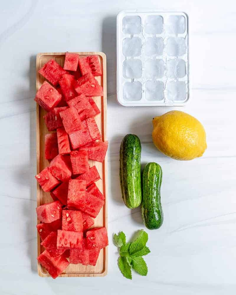 watermelon cooler ingredients consisting of cut up watermelon, 2 zucchinis, 1 lemon, mint leaves, and ice in an ice tray with a white marble background