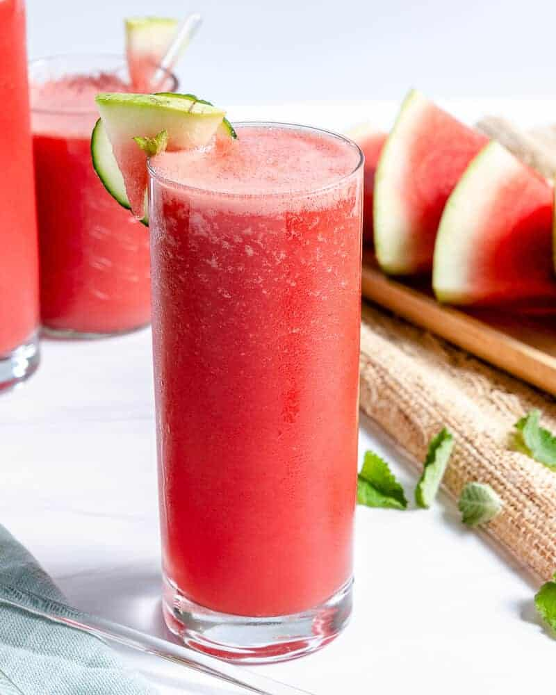 watermelon cooler in tall glass cup with sliced watermelon and more cups of watermelon cooler in a white background