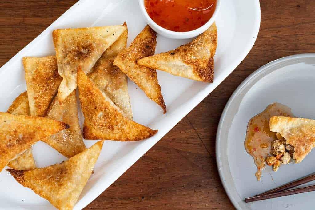Crispy Fried Tofu Wontons Served with Hot Sauce on a long platter