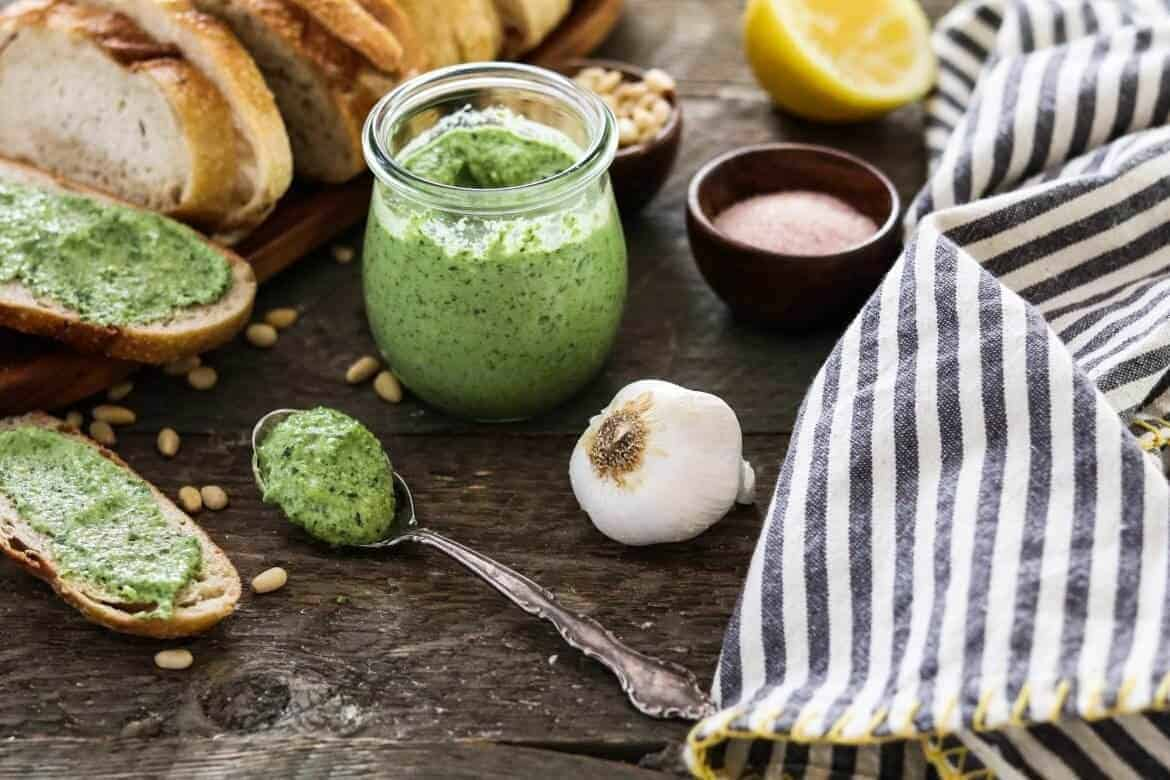 zucchini pesto in glass jar with various ingredients in the background along with a gray and white cloth