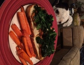 An open faced tofu and kale sandwich with a side of roasted carrots on a plate.
