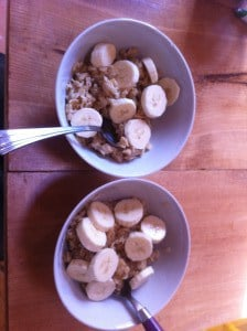 Two bowls of warm oatmeal topped with banana slices.