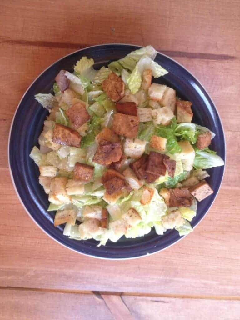 Dinner plate filled with caesar salad with croutons and tofu.