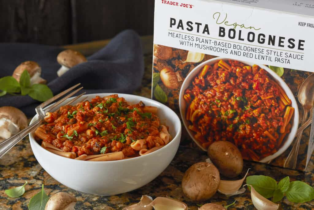 vegan pasta bolognese packaging with product in a white bowl against a dark background