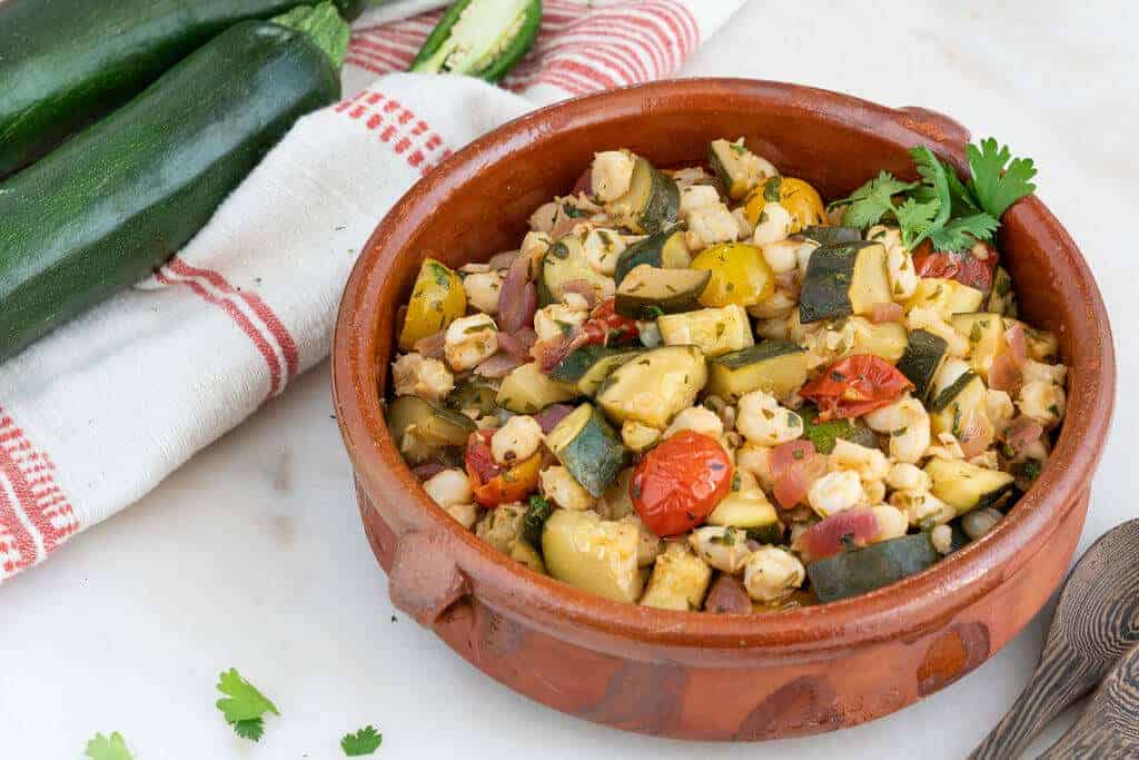 brown bowl with zucchini and hominy with a red and white cloth in a white background
