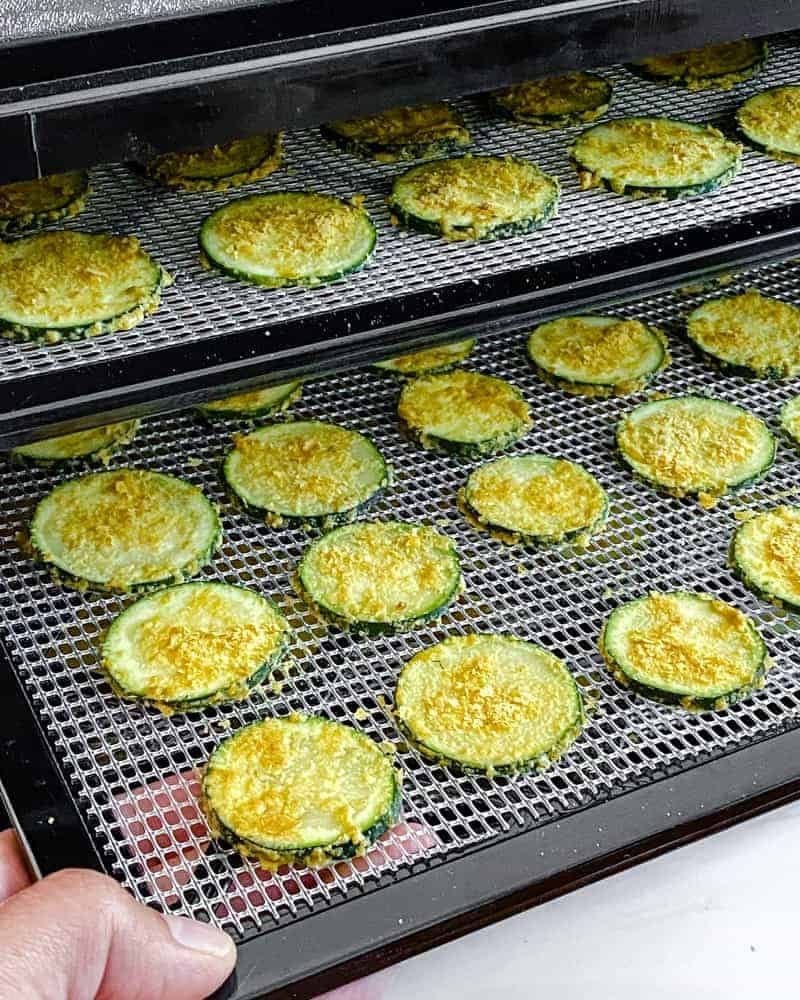uncooked cheesy zucchini chips on two layered rack