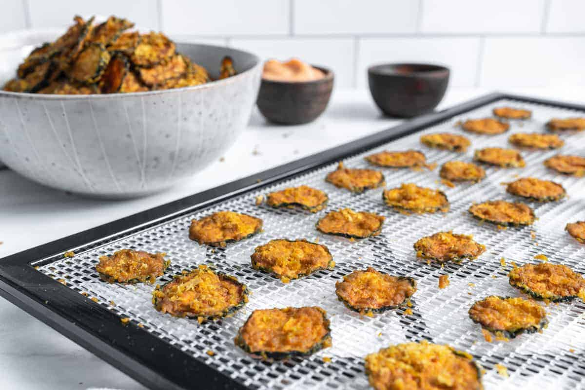 cooked cheesy zucchini chips on rack with a bowl or chips in the background
