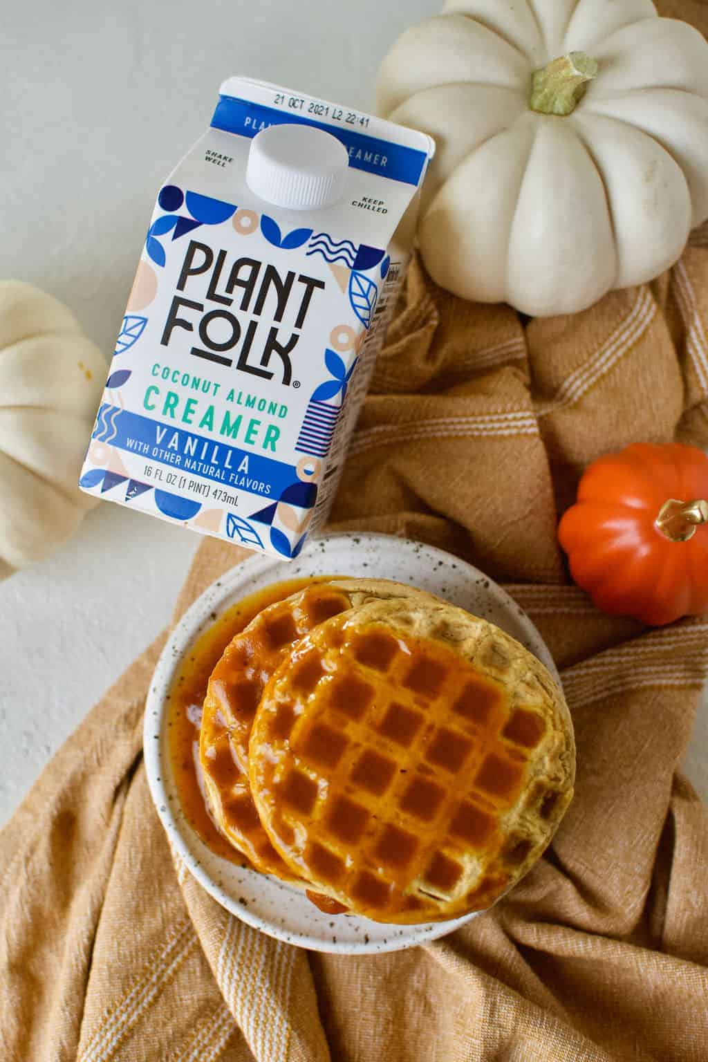 completed waffles on a plate plant folk creamer and pumpkins in the background
