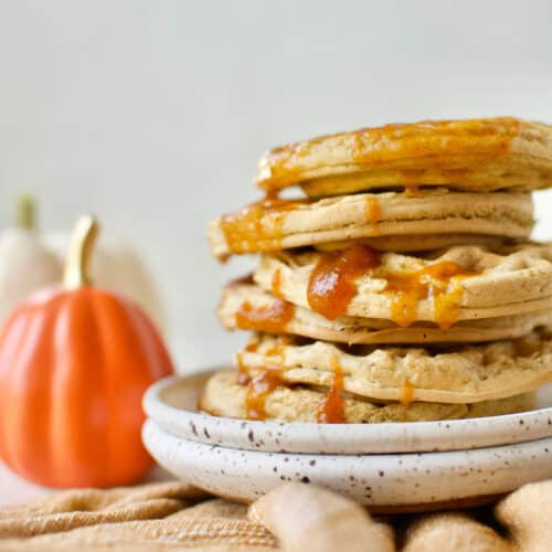 completed Vegan Pumpkin Waffles stacked on top of one another on a white plate with a pumpkin in the background