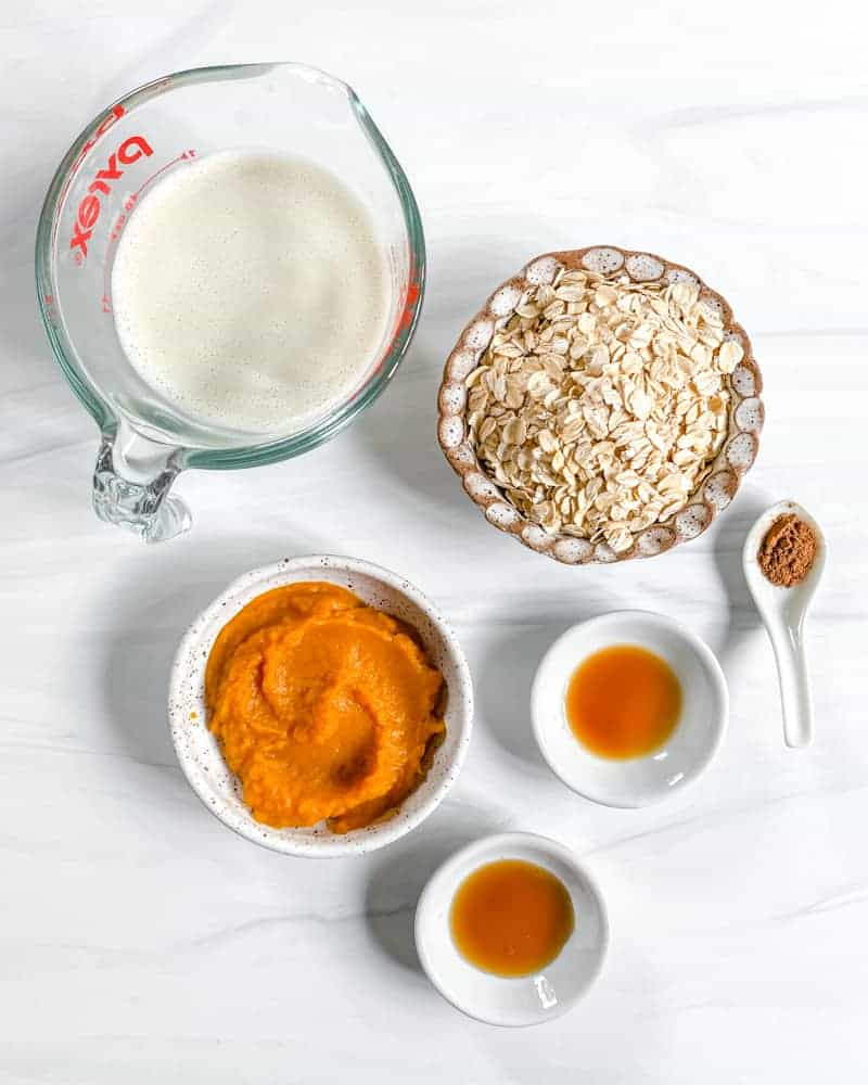 Pumpkin Overnight Oats Ingredients against a white marble background