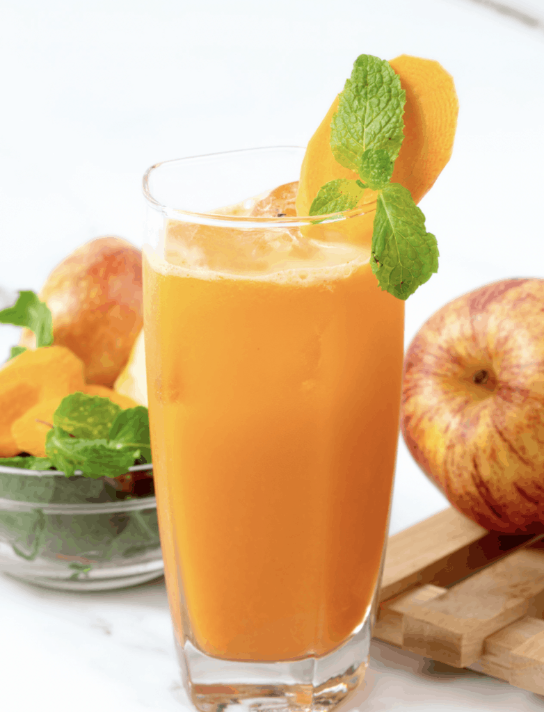 finished carrot apple ginger juice in a glass with ingredients in the background