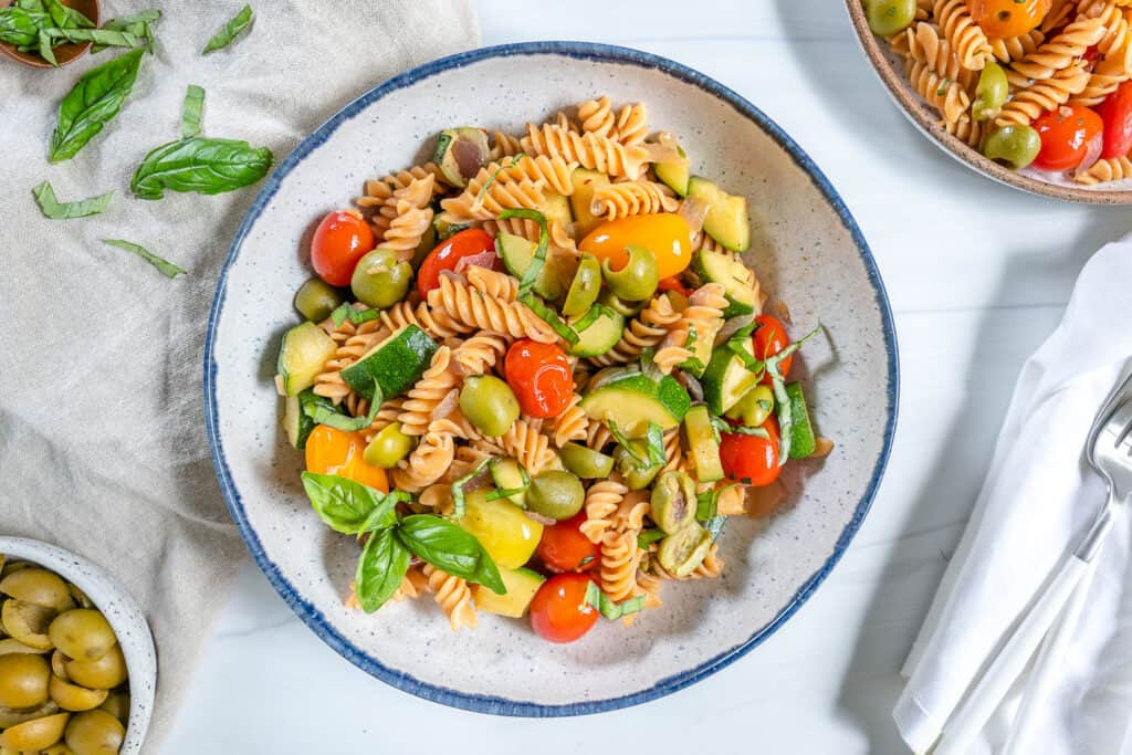 finished summertime pasta in a white plate with ingredients spread out in the background