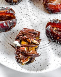 stuffed dates process showing date with melted chocolate on top on white plate