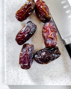 Pumpkin Stuffed Dates process showing 6 whole on white cutting board with knife