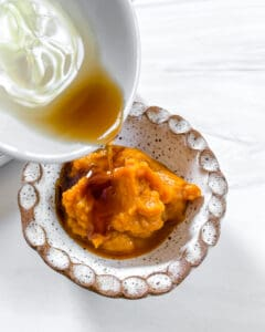 stuffed dates process showing wet ingredients being poured into pumpkin puree bowl against white background