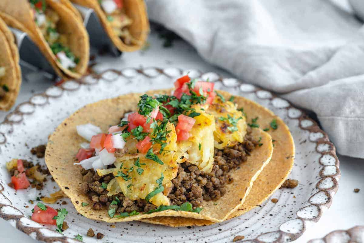 Breakfast Tacos in a white plate with tacos and ingredients in the background against white surface