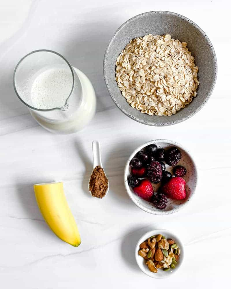 stovetop yogurt in a white bowl in a white background with ingredients in the background