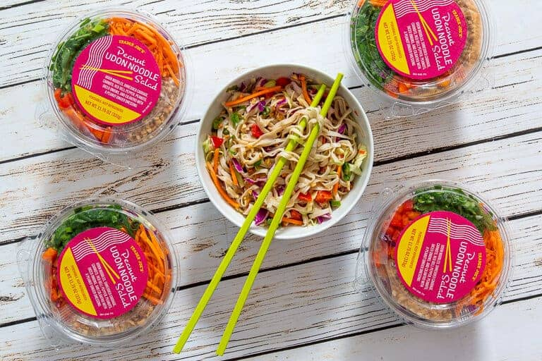 peanut udon salad packaging with a white bowl of the noodles against a gray/white background