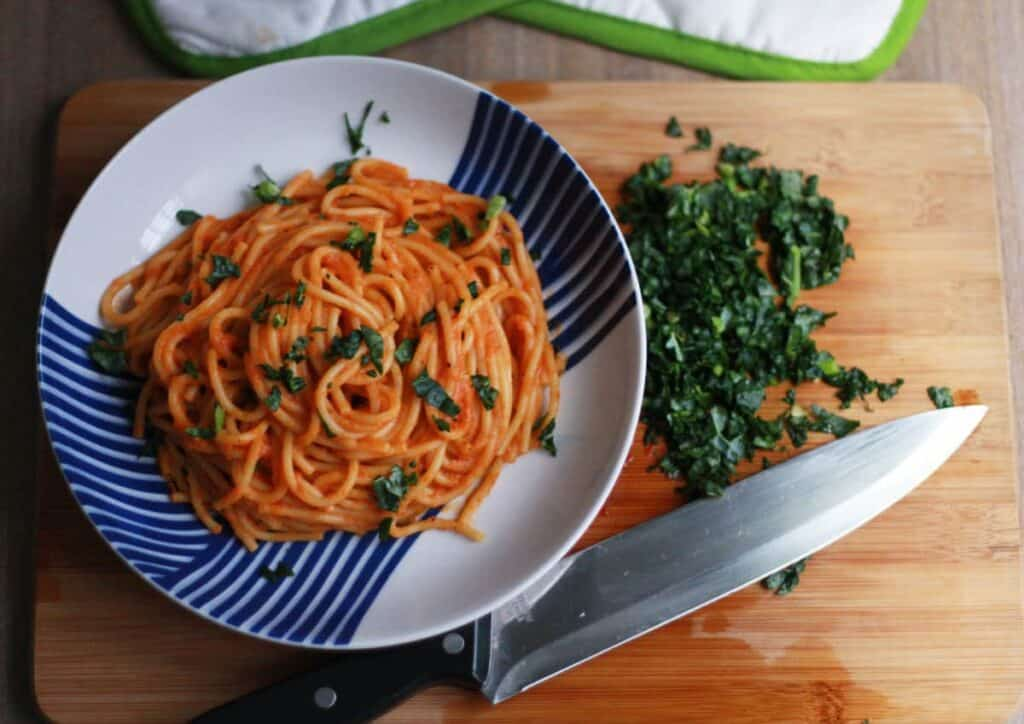 finished spaghetti on a blue and white plate with ingredients in the background on top of a wooden surface