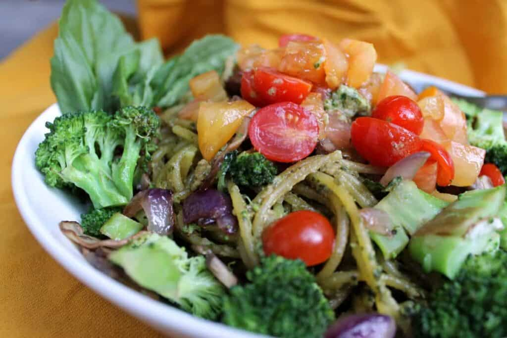 finished sunflower seed pesto in a white plate mixed iwth veggies against a dark background