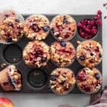finished apple berry muffins in muffin tray against a white background