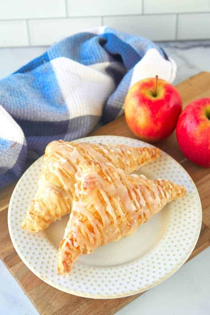 finished vegan apple turnovers on a white plate with apples and a towel in the background