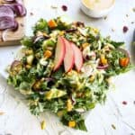 finished salad against a white surface with ingredients scattered in the background