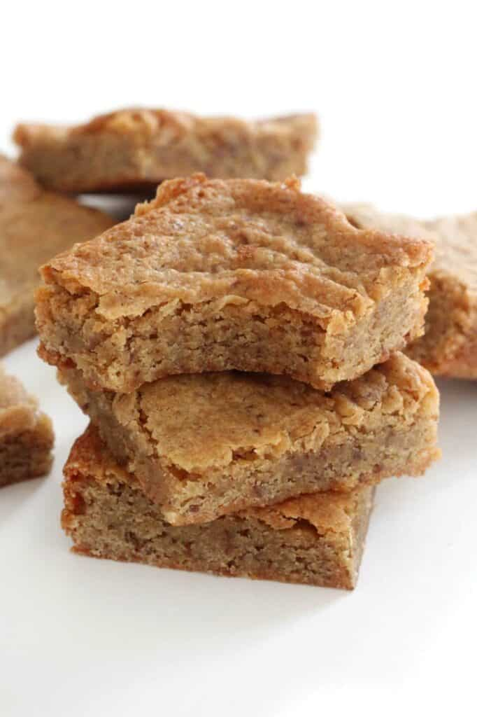 finished gluten free maple blondies stacked on each other against a white background